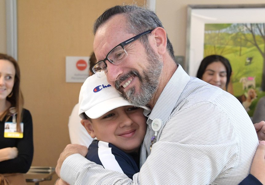 Provider hugging patient on last day of chemotherapy