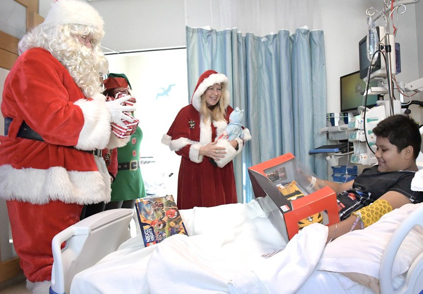 Santa giving a gift to a patient at Cottage Children's Medical Center