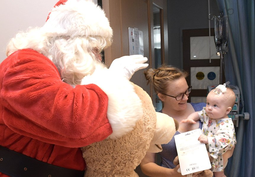 Santa paying a visit to a toddler at Cottage Children's Medical Center