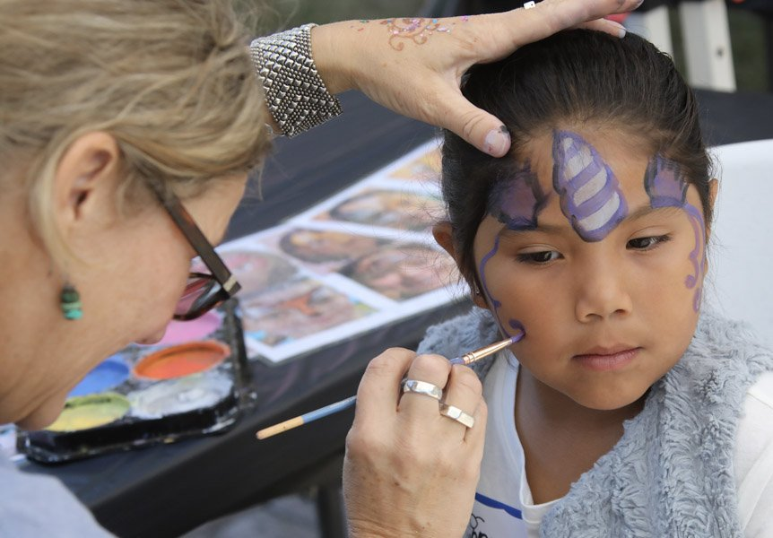 Child enjoying getting their face painted at the NICU Reunion