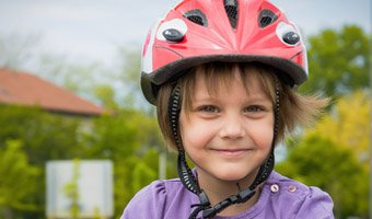 Child smiling and wearing a safety helmet