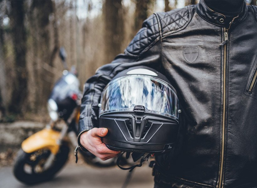 Motorcyclist holding a helmet and standing in front of their motorcycle