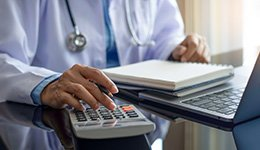 A clinical professional sitting at a laptop with a calculator