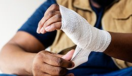 An injured hand being wrapped in gauze